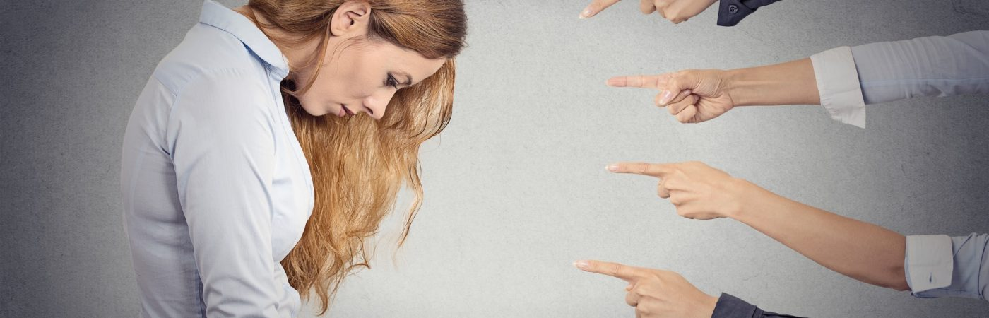 Concept of accusation of guilty businesswoman. Side profile portrait sad upset woman looking down many fingers pointing at her isolated grey office background. Human face expression emotion feeling